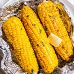 three grilled cobs of corn in opened foil packet on white plate with butter and chopped parsley