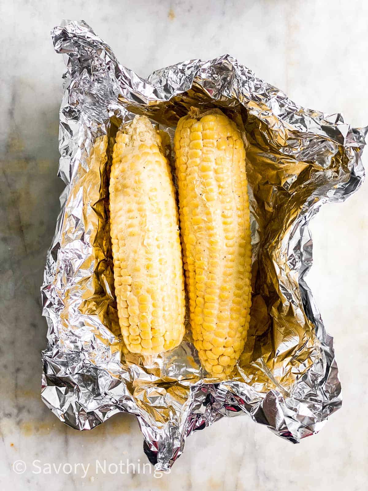 two raw ears of corn covered in butter sitting in aluminium foil boat