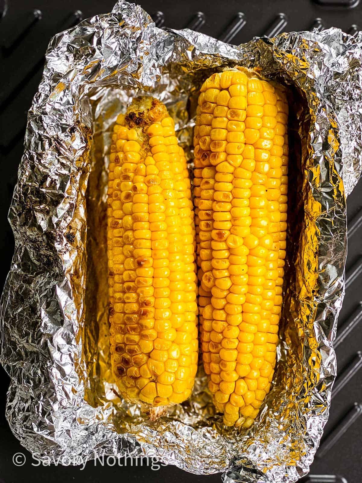 charred corn on the cob in opened foil packet on grill
