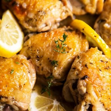 close up photo of lemon chicken thighs on plate with lemon slices