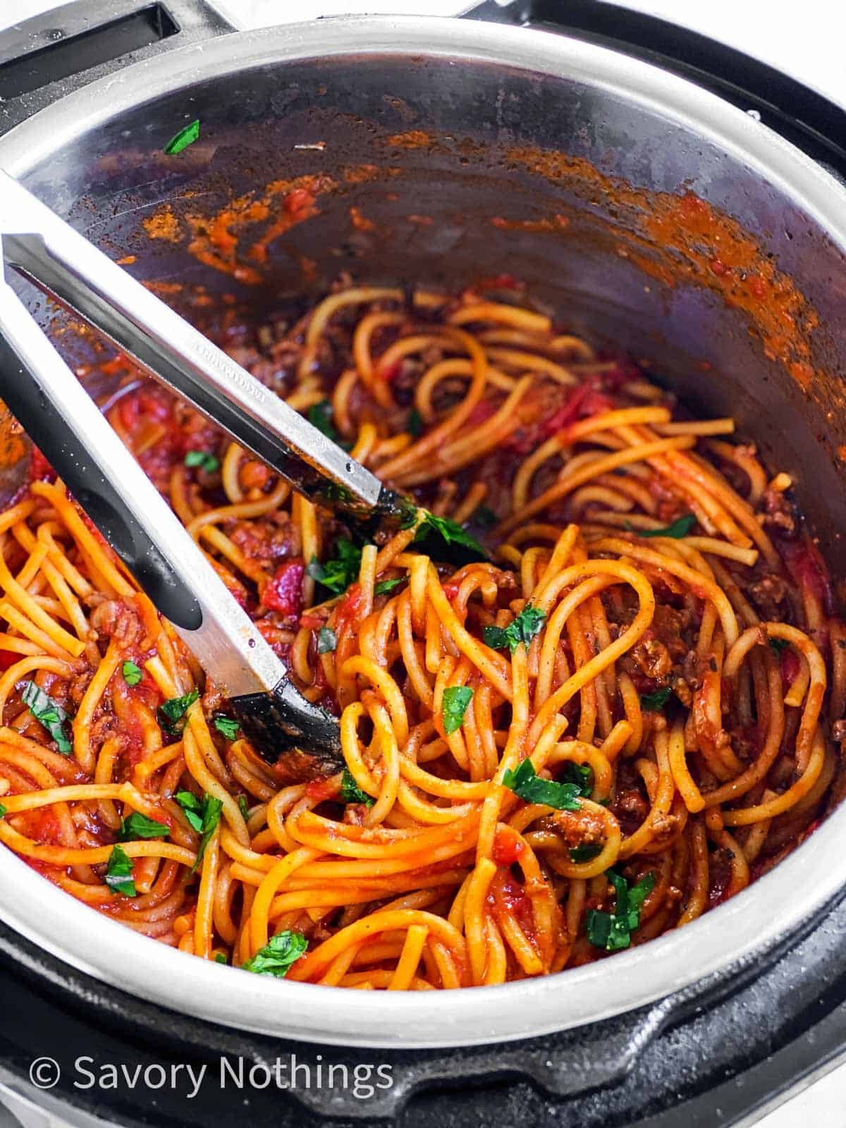 frontal view of spaghetti and meat sauce in instant pot with kitchen tongs