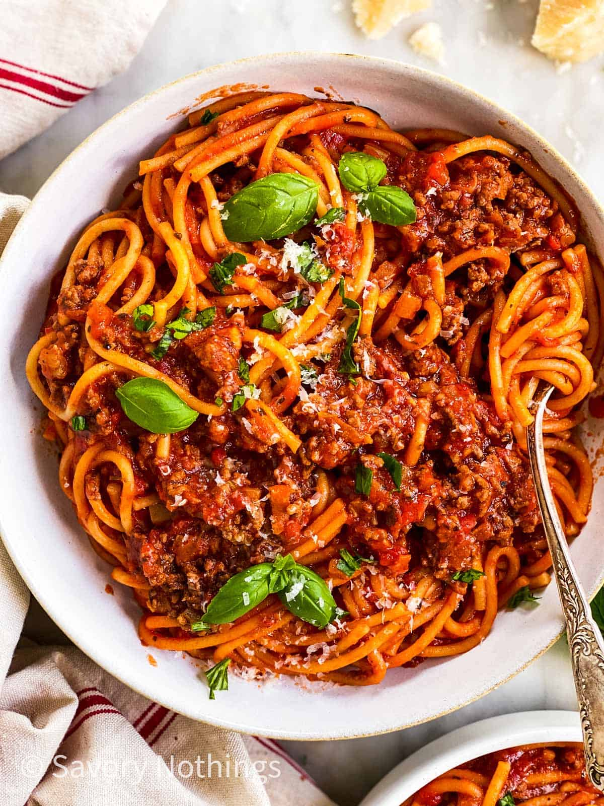 close up photo of white plate filled with spaghetti and meat sauce and garnished with fresh basil