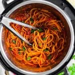 overhead view of instant pot filled with spaghetti and meat sauce with kitchen tongs stuck in