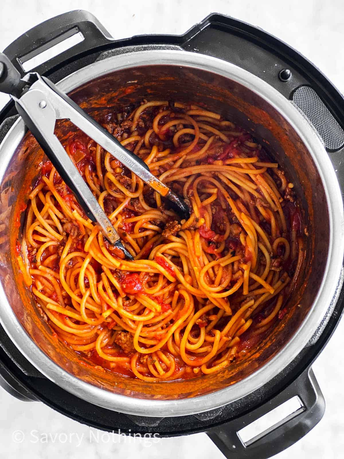 cooked spaghetti in meat sauce in instant pot with kitchen tongs