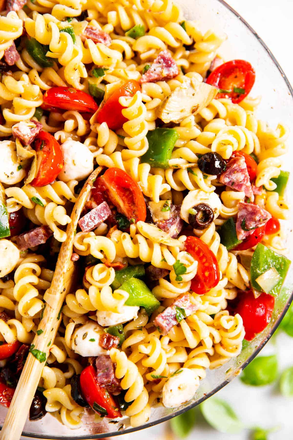 overhead close up photo of Italian pasta salad in glass bowl with wooden spoon inside salad
