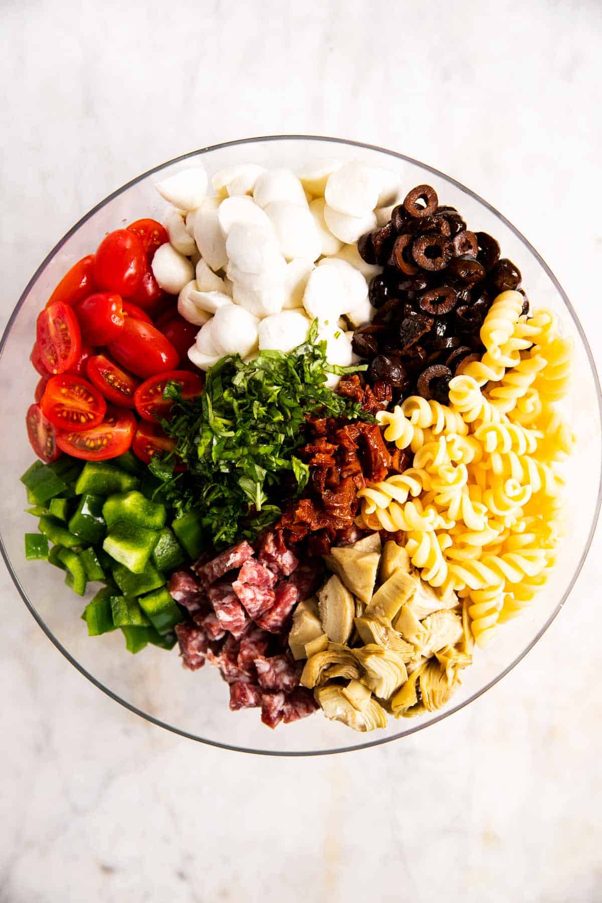 overhead view of ingredients for Italian pasta salad arranged in glass bowl