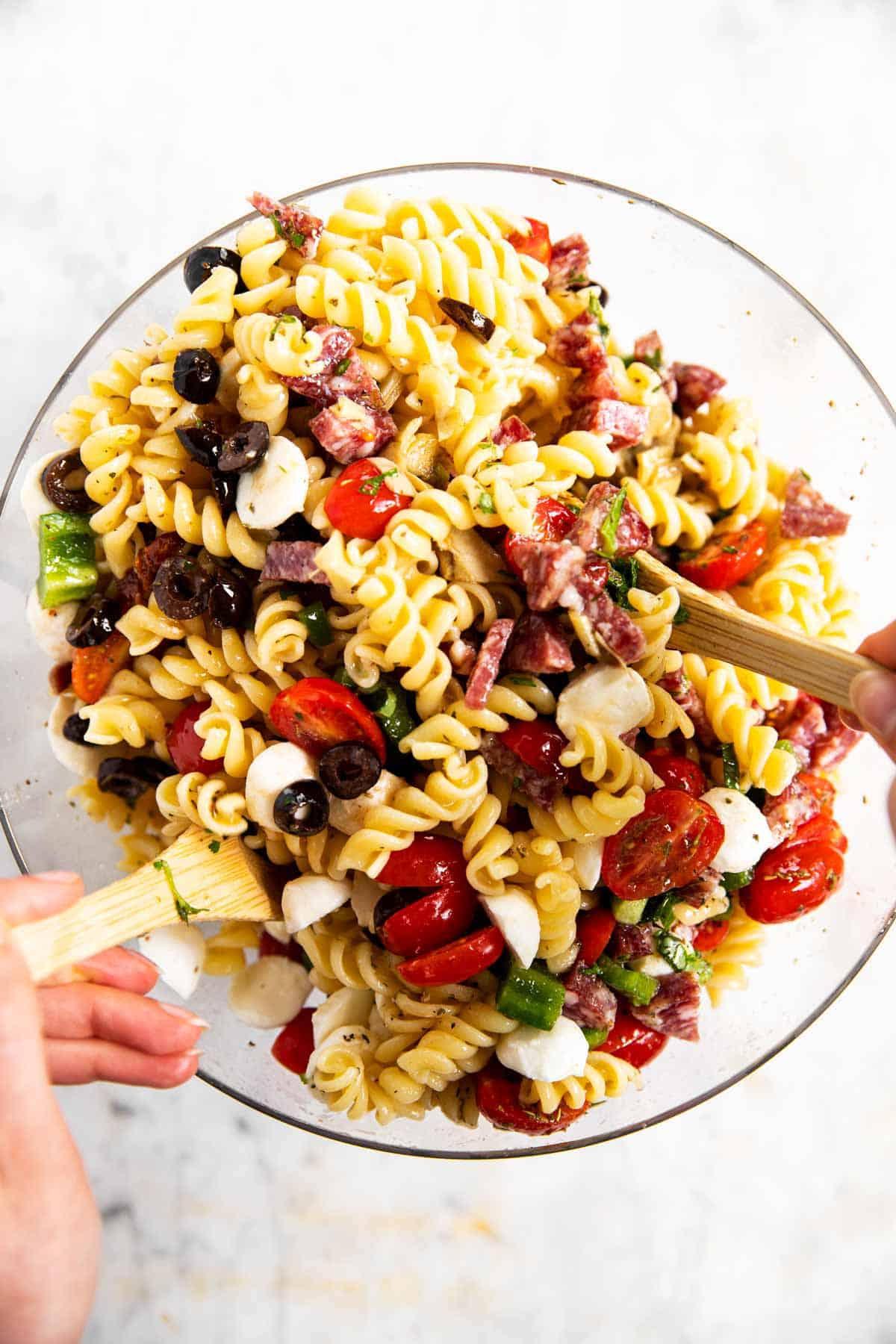 female hands using wooden salad tongs to toss Italian pasta salad in glass bowl