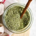 overhead view of homemade Italian seasoning in small glass jar with ceramic spoon