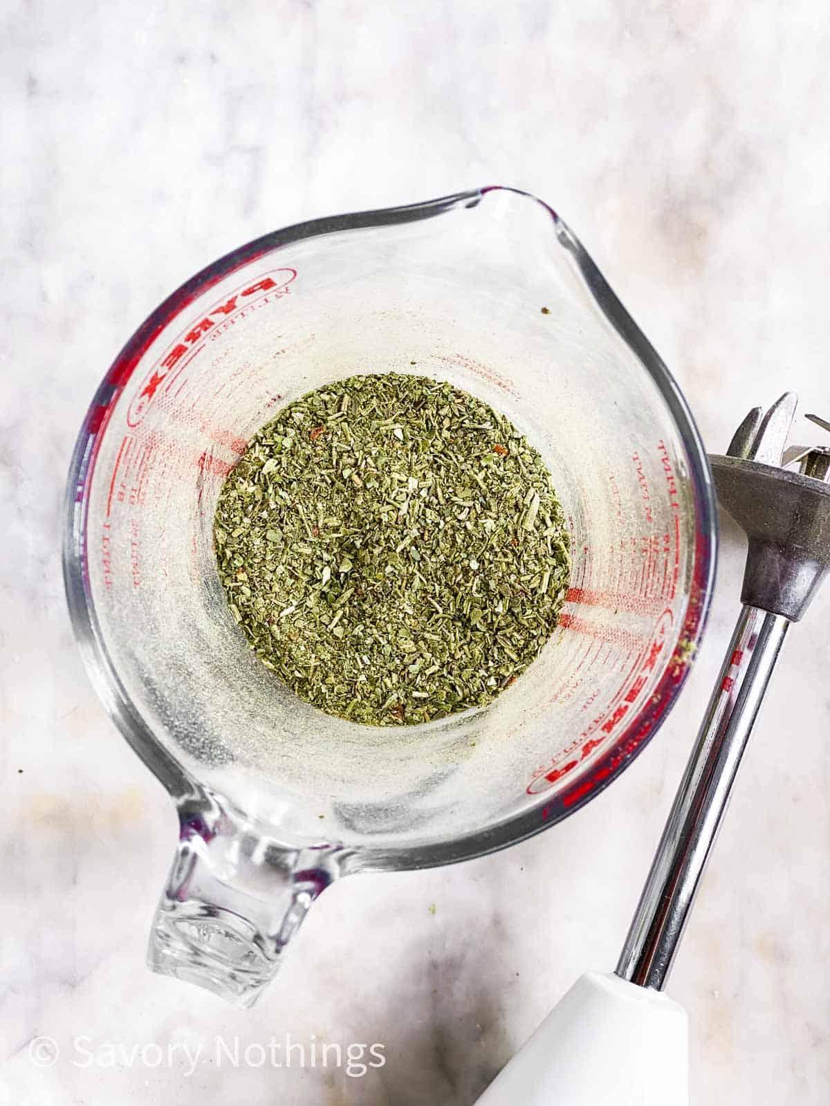 homemade Italian seasoning in glass measuring jug next to an immersion blender