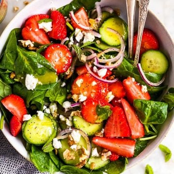 overhead close up view of white bowl with strawberry spinach salad