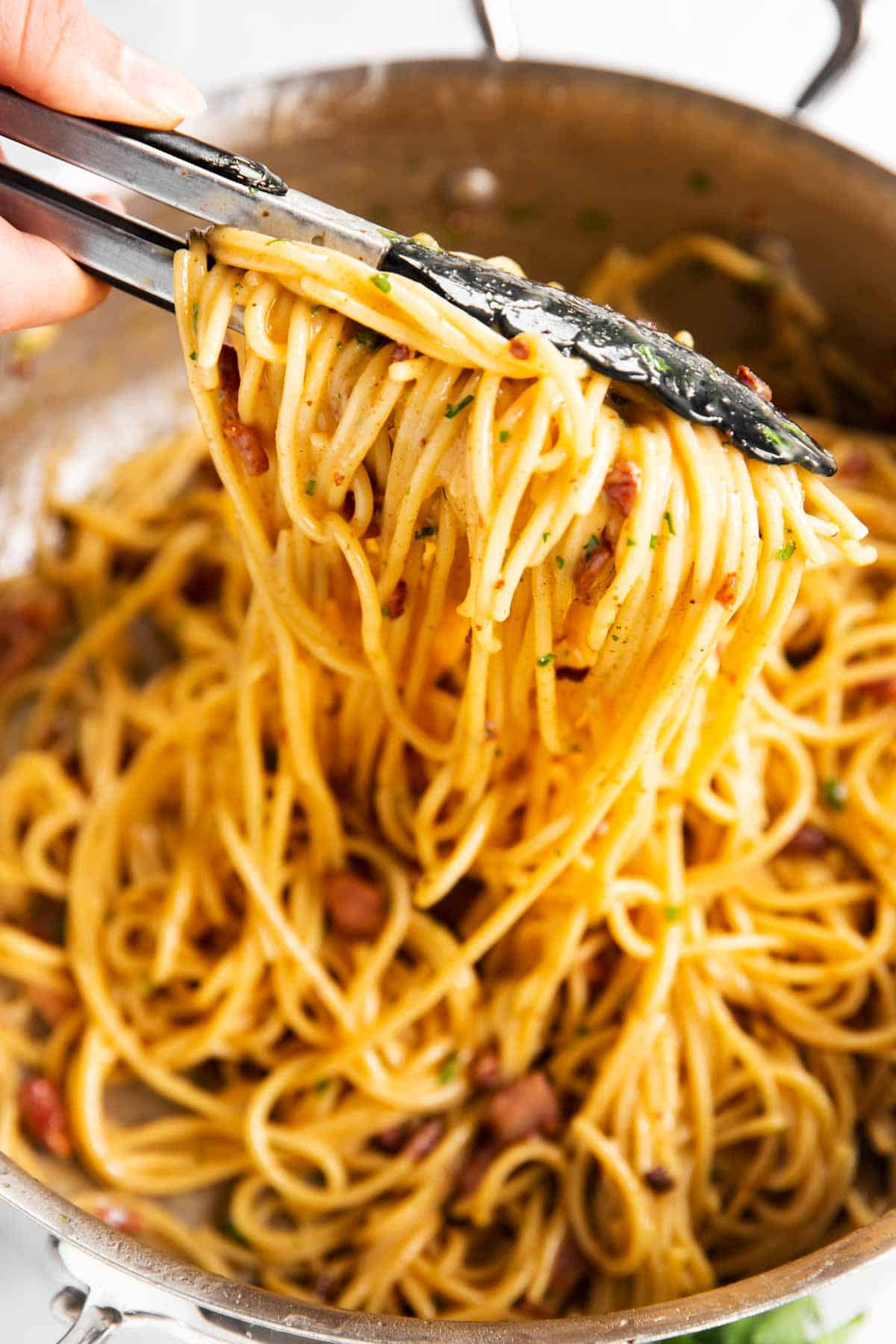 pulling spaghetti carbonara from stainless steel pan with kitchen tongs