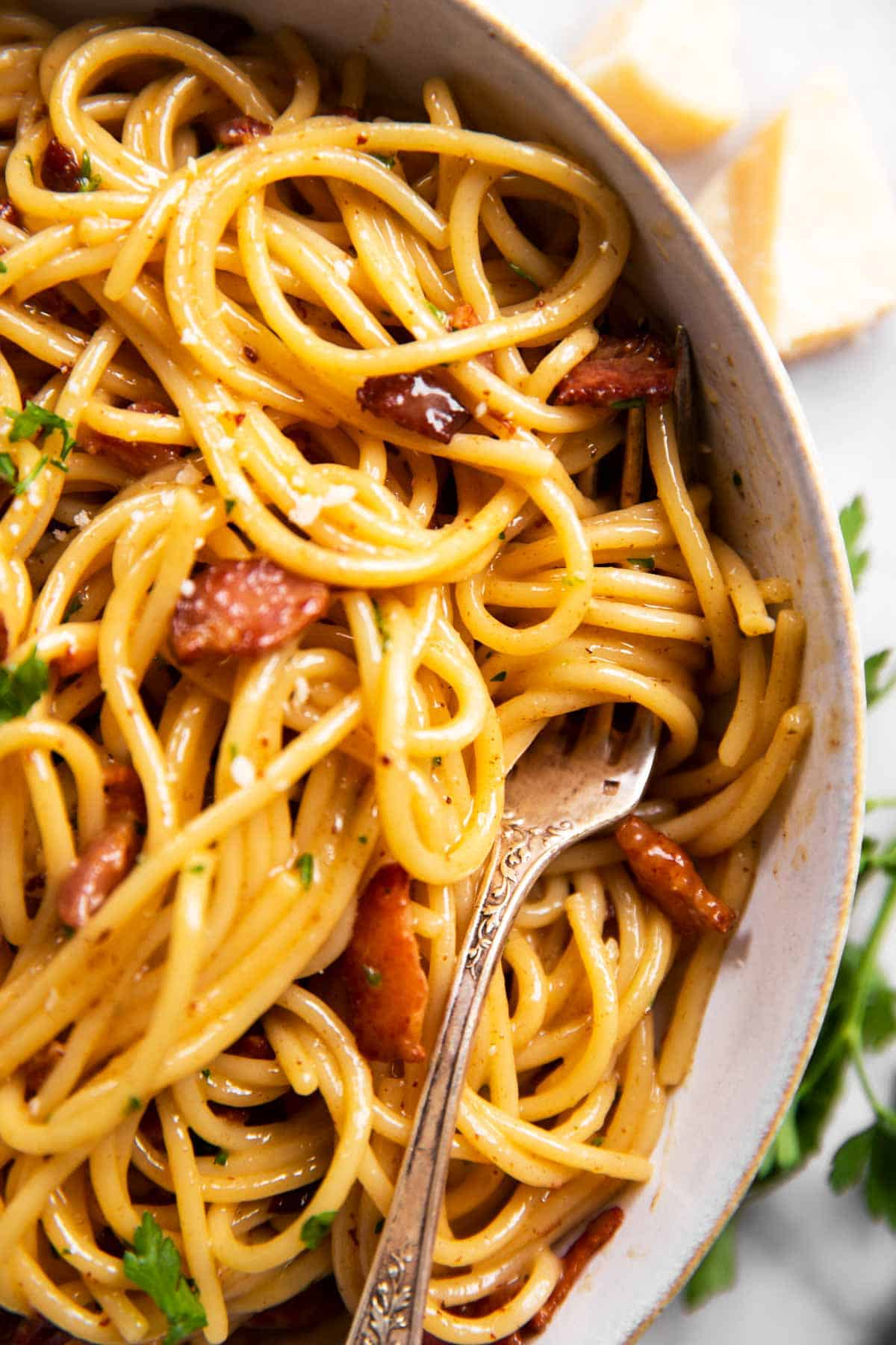 close up photo of fork on white pate with spaghetti carbonara