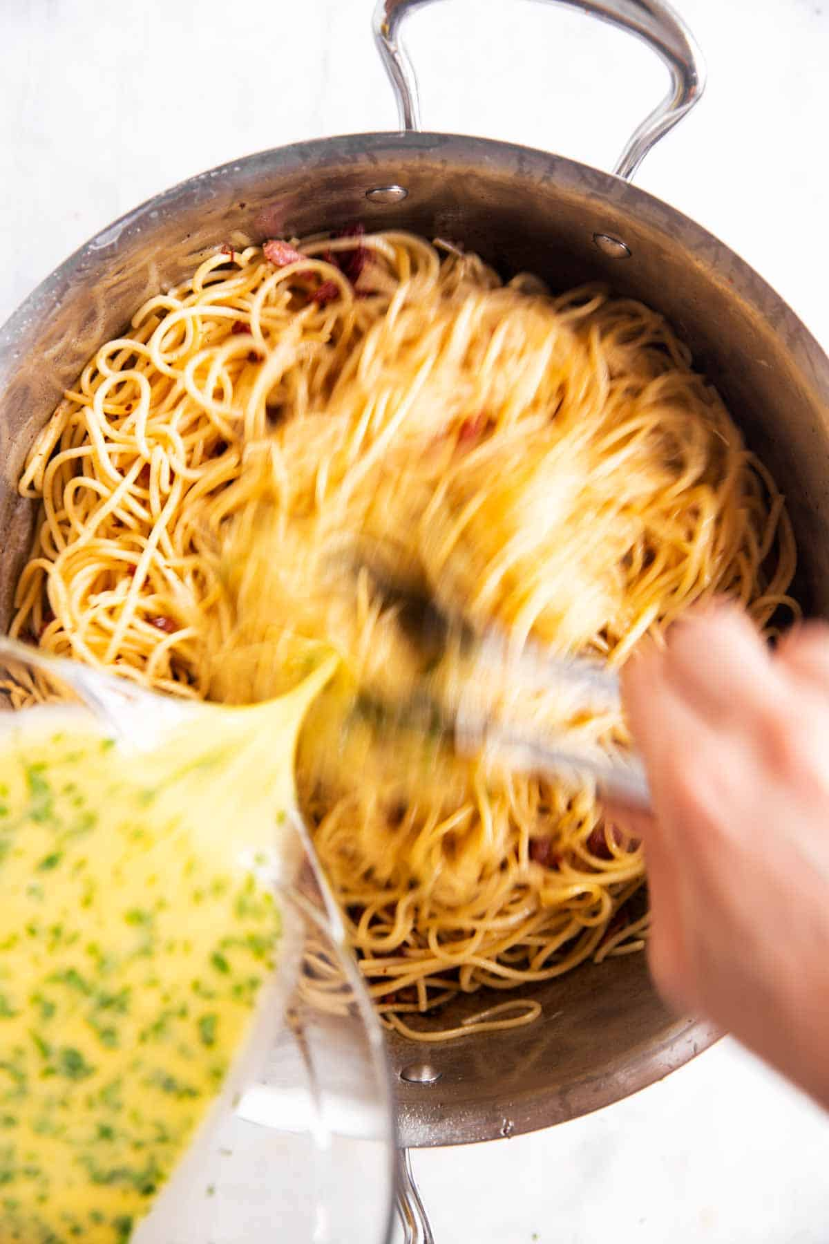 female hand tossing spaghetti with beaten eggs in stainless steel skillet