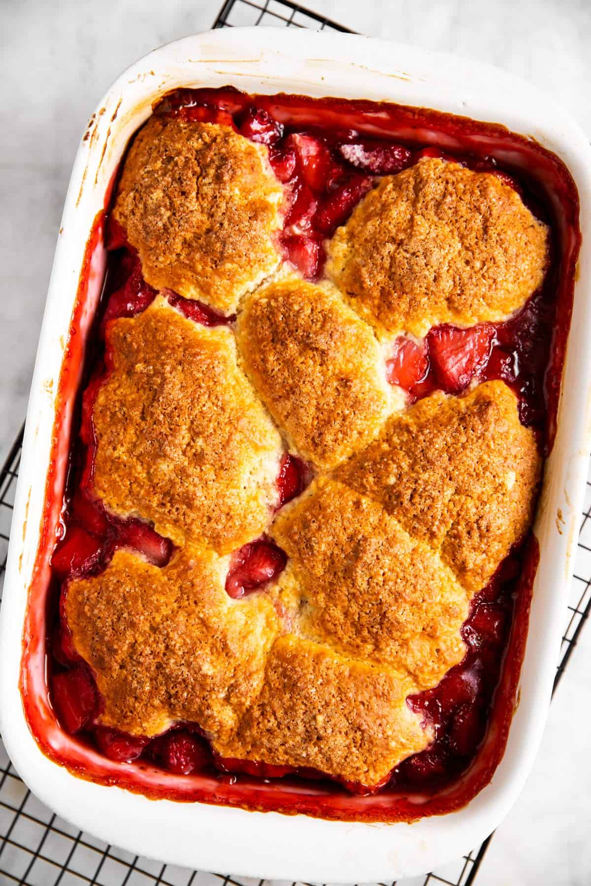 baked strawberry cobbler in white rectangular casserole dish on top of black cooling rack