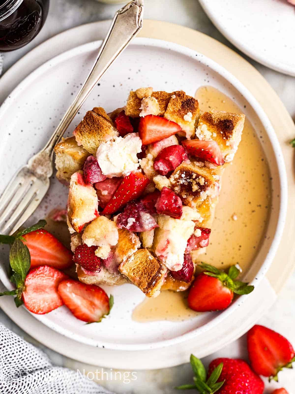 overhead view of a slice of strawberry French toast casserole on a white plate with maple syrup