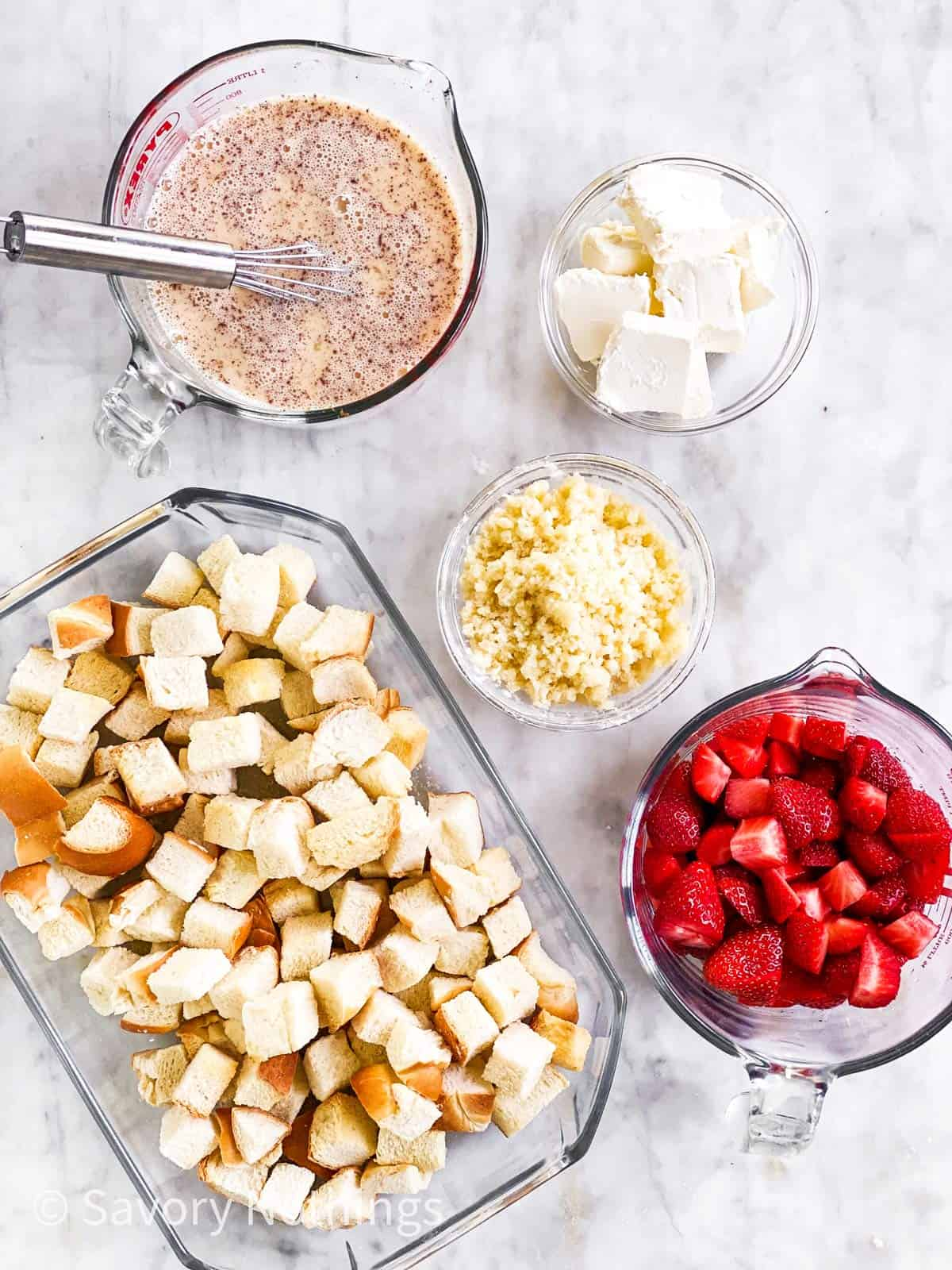 assembled ingredients for strawberry French toast casserole on marble surface