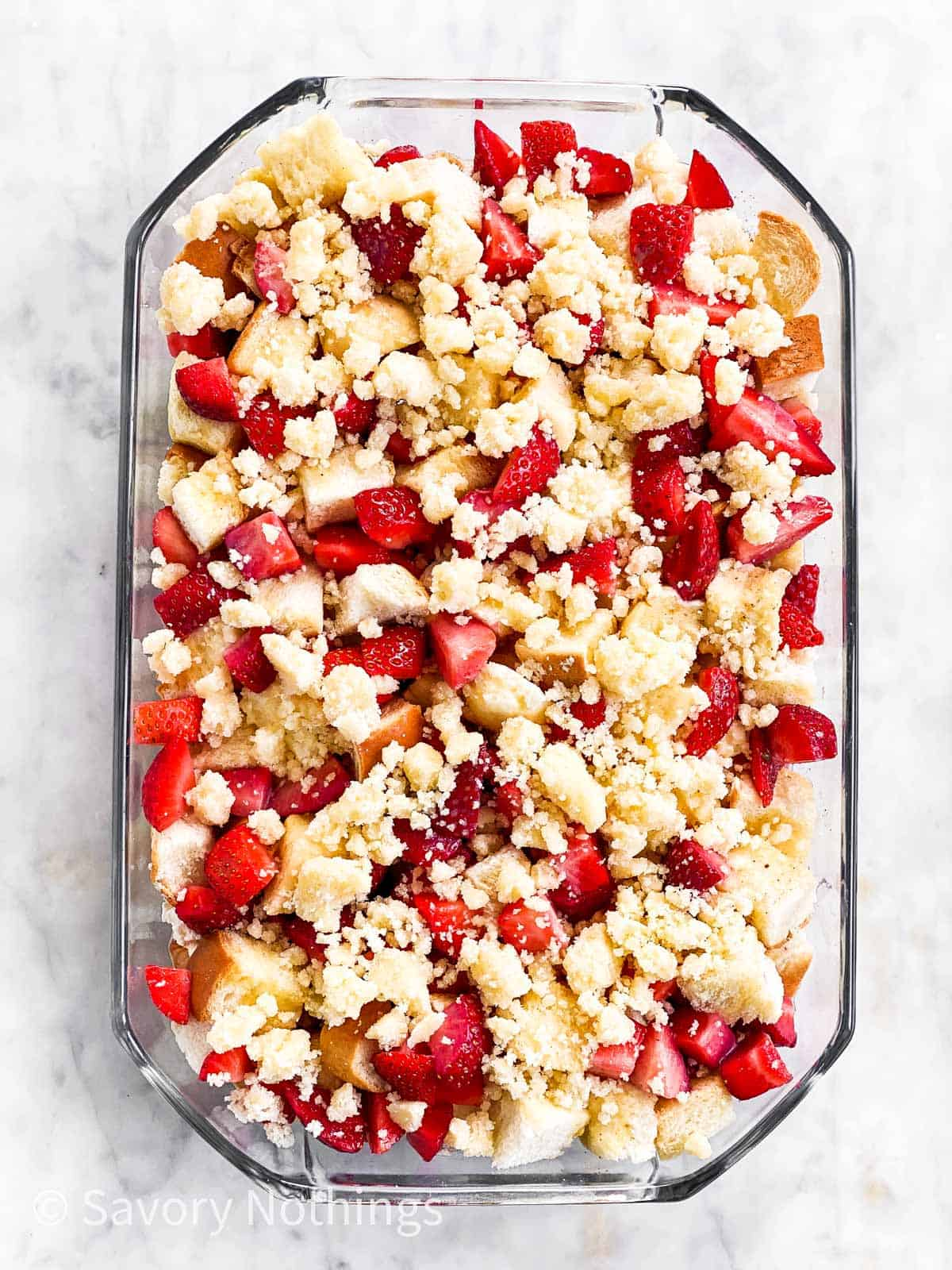 unbaked strawberry French toast casserole in glass dish sitting on marble surface, topped with streusel