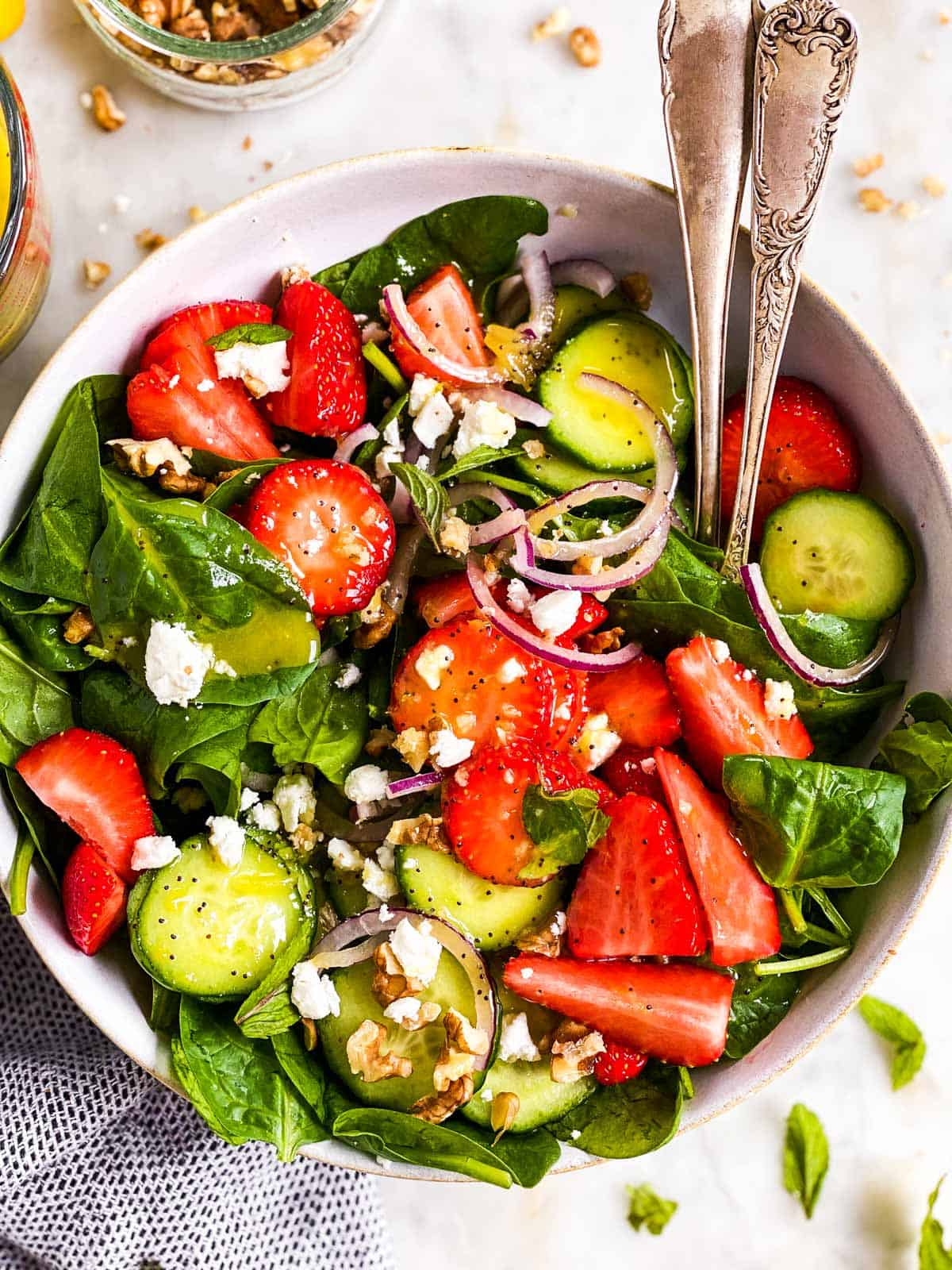 bowl with strawberry spinach salad and lemon poppy seed dressing in white salad bowl