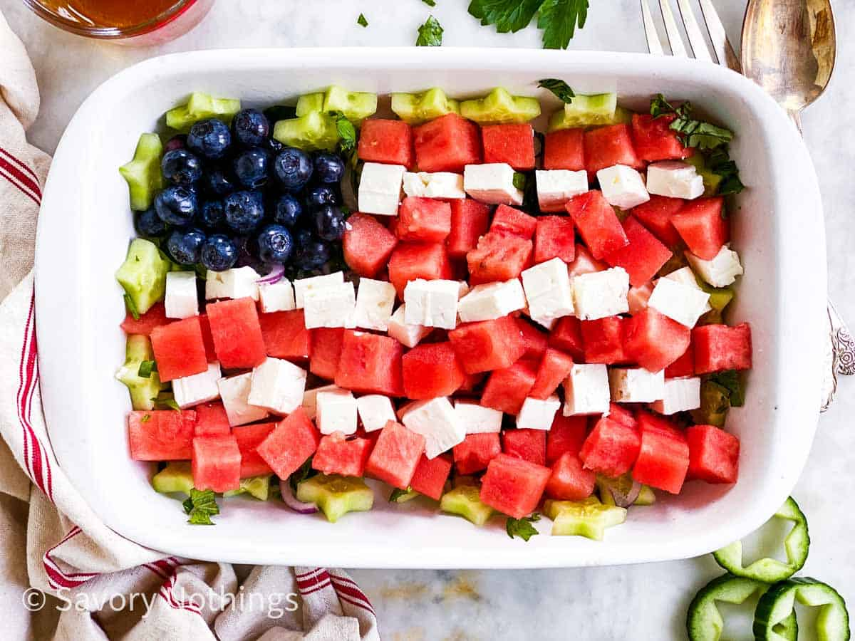 watermelon. feta cheese and blueberries arranged as American flag in rectangular white dish