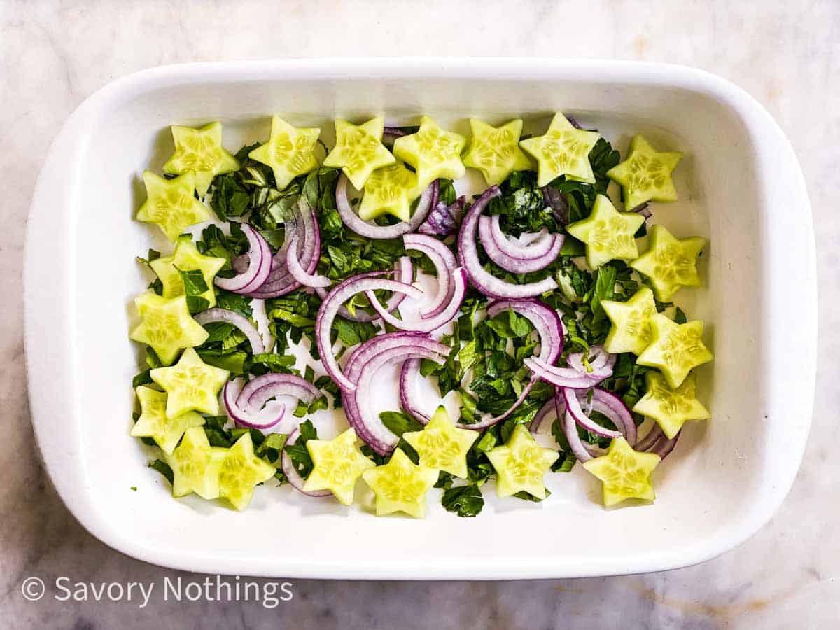 chopped herbs, sliced red onion and cucumber star cutouts in rectangular white dish