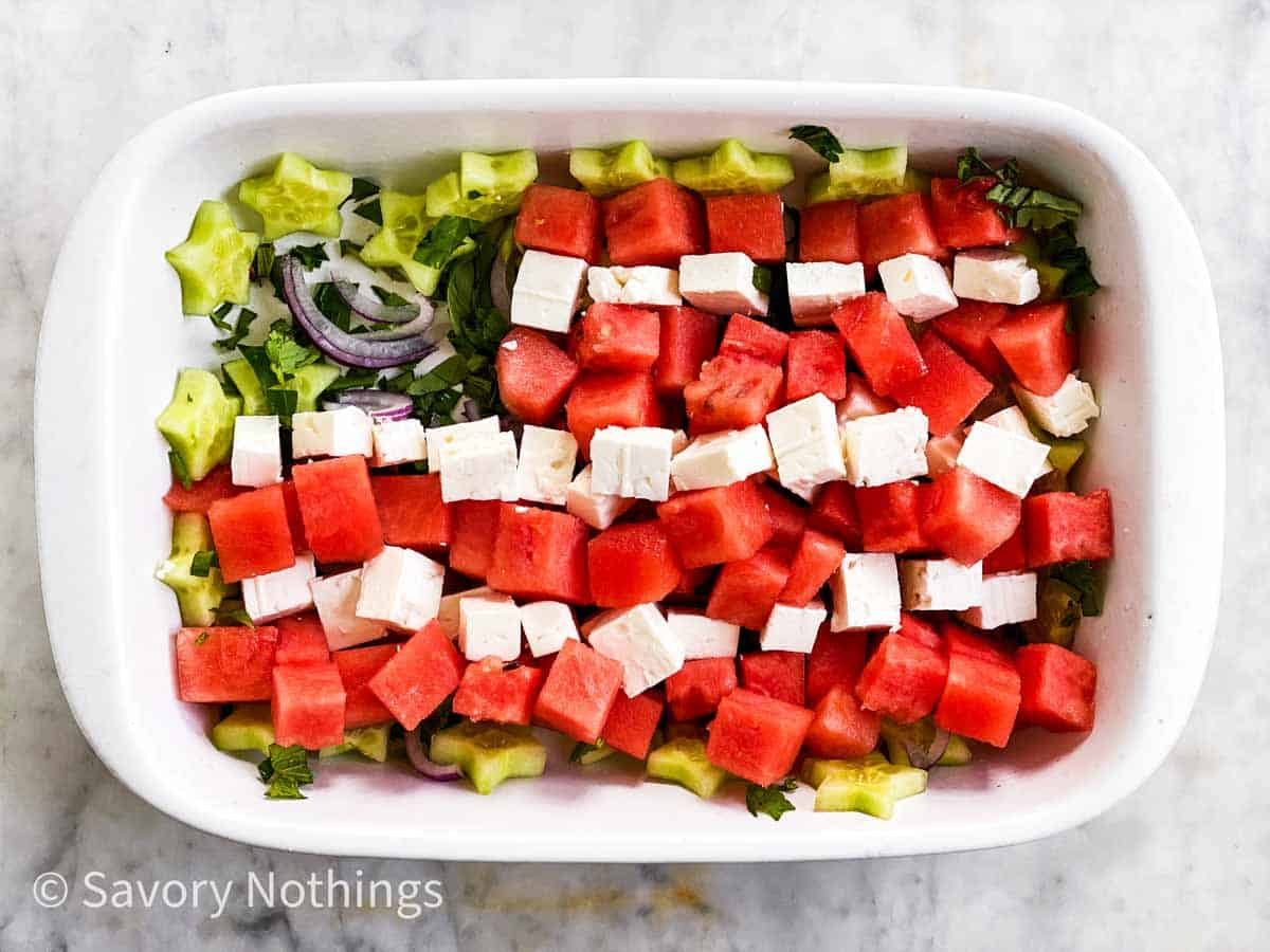 watermelon and feta cheese arranged in stripes over cucumber stars, herbs and red onion in rectangular white dish
