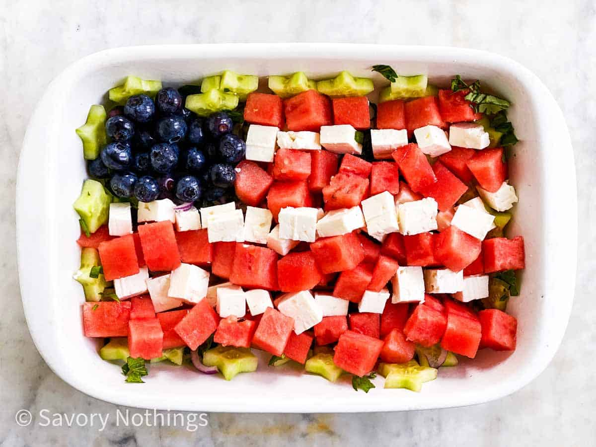 blueberries, feta cheese and watermelon cubes arranged as US flag in white rectangular dish