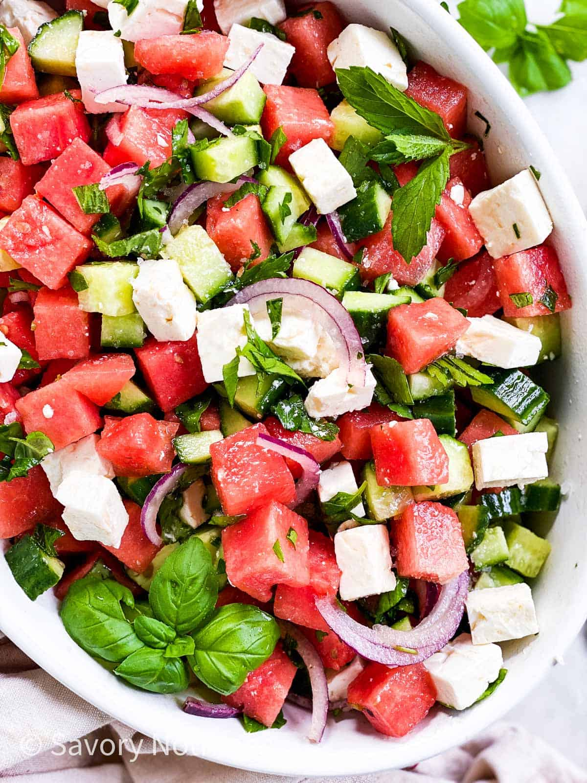 overhead close up of oval white dish with watermelon salad