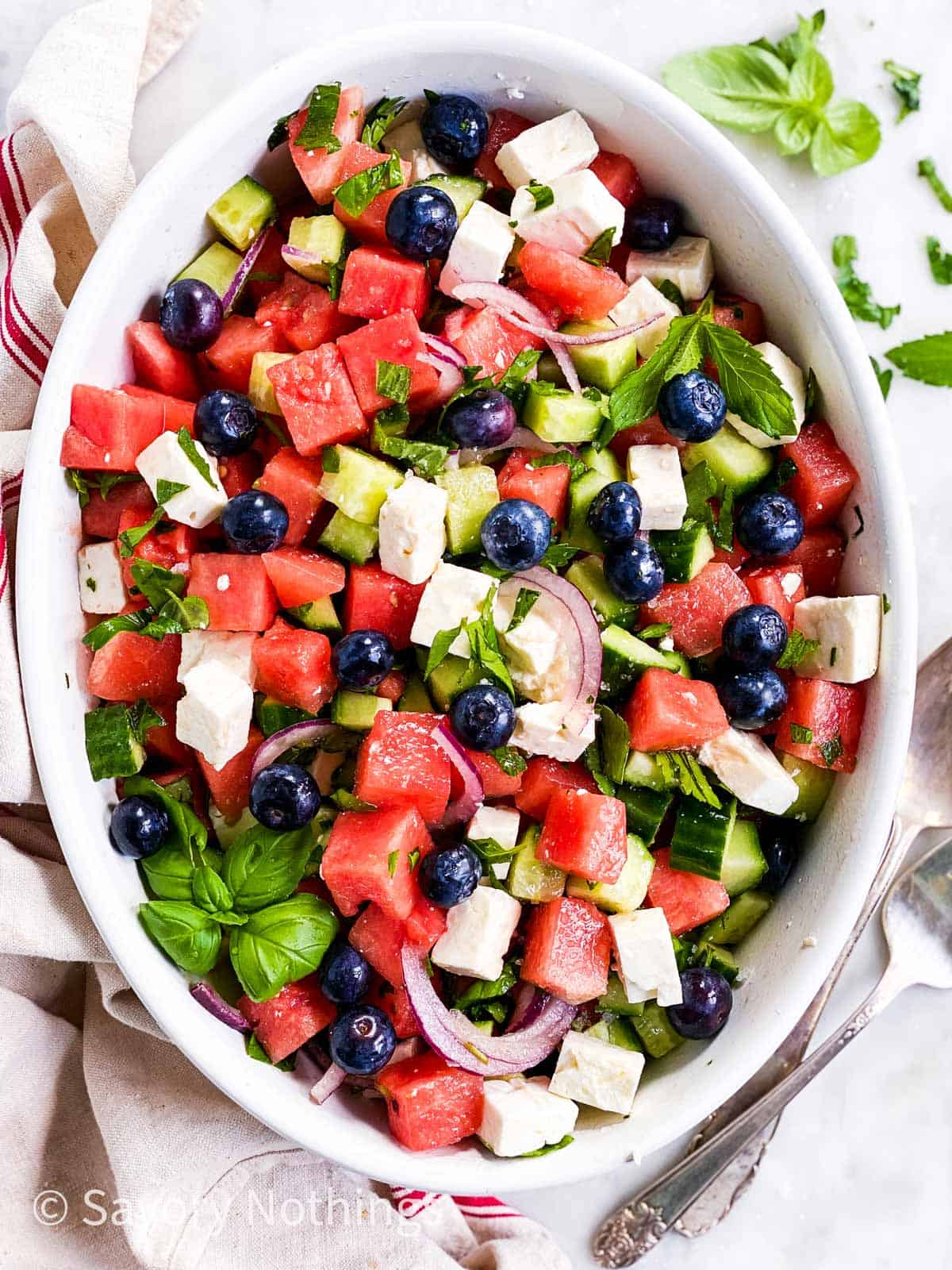 watermelon and feta salad with blueberries in white oval dish