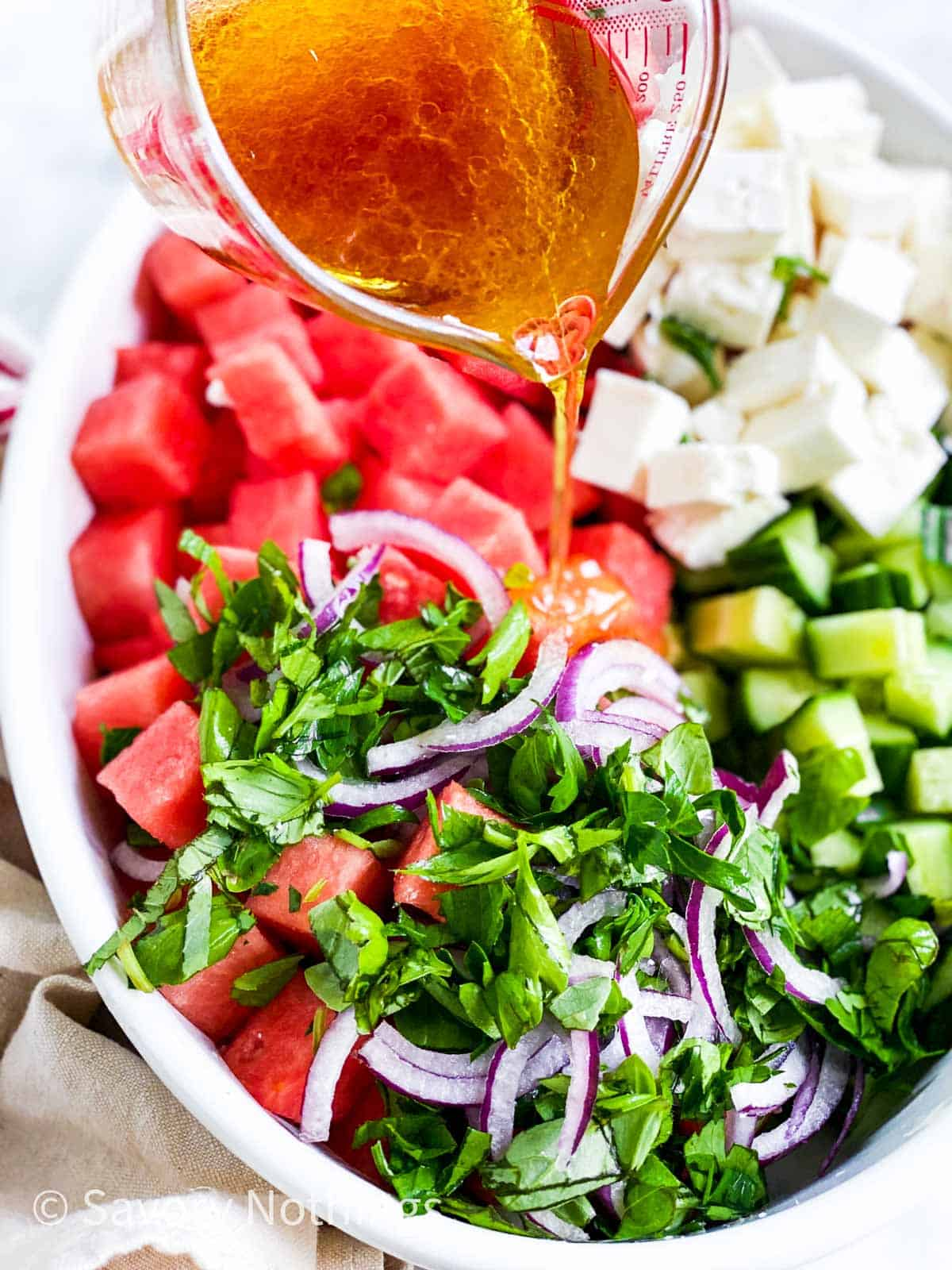 vinaigrette pouring from glass jug over ingredients for watermelon salad