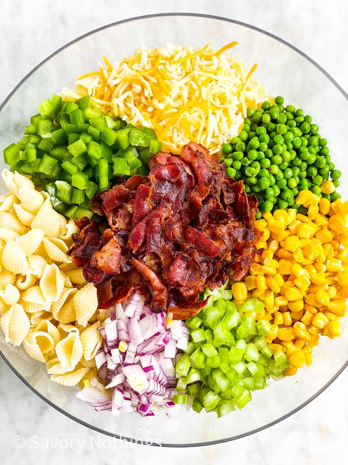 overhead view of ingredients for bacon ranch pasta salad in glass bowl