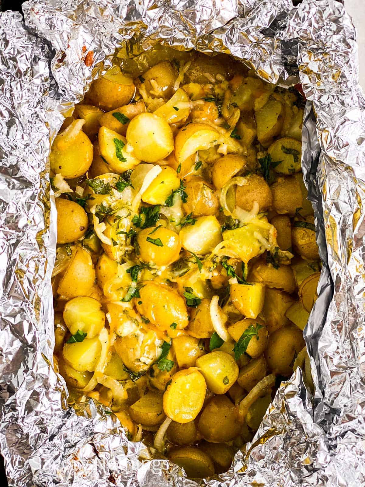 close up photo of cheesy campfire potatoes in foil pouch