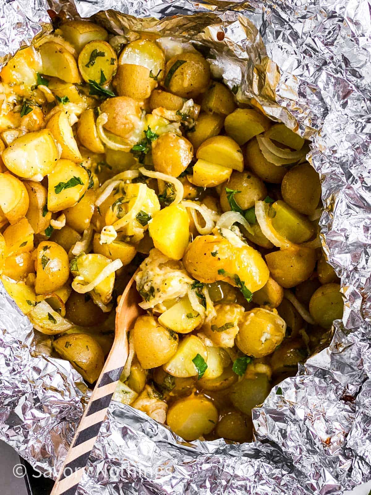 overhead view of cheesy campfire potatoes in foil packet with disposable fork stuck inside
