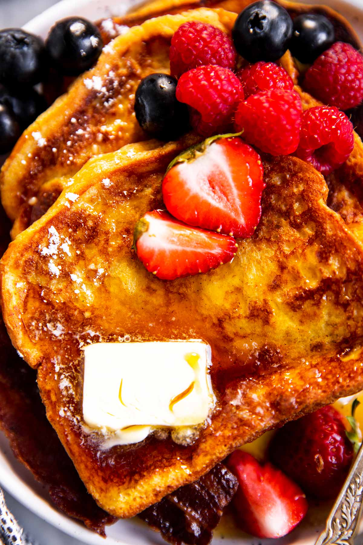 close up photo of French toast on plate with butter, maple syrup and fresh berries