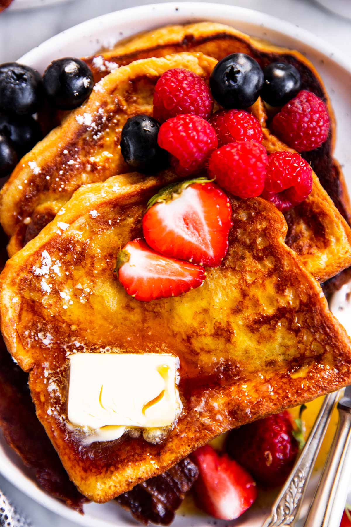 overhead view of slices of French toast garnished with icing sugar, butter and berries