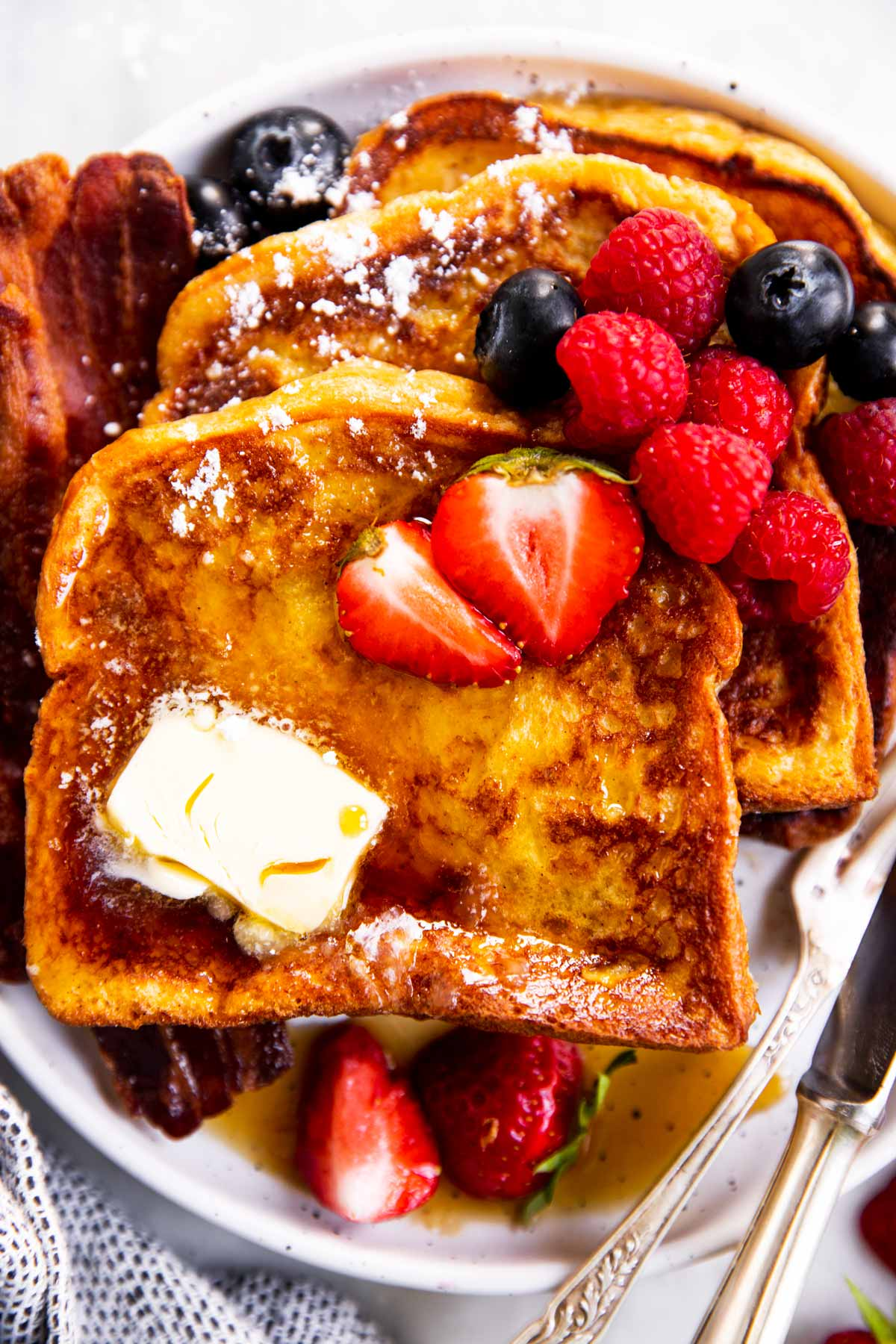 three slices of French toast on white plate with butter, bacon and berries