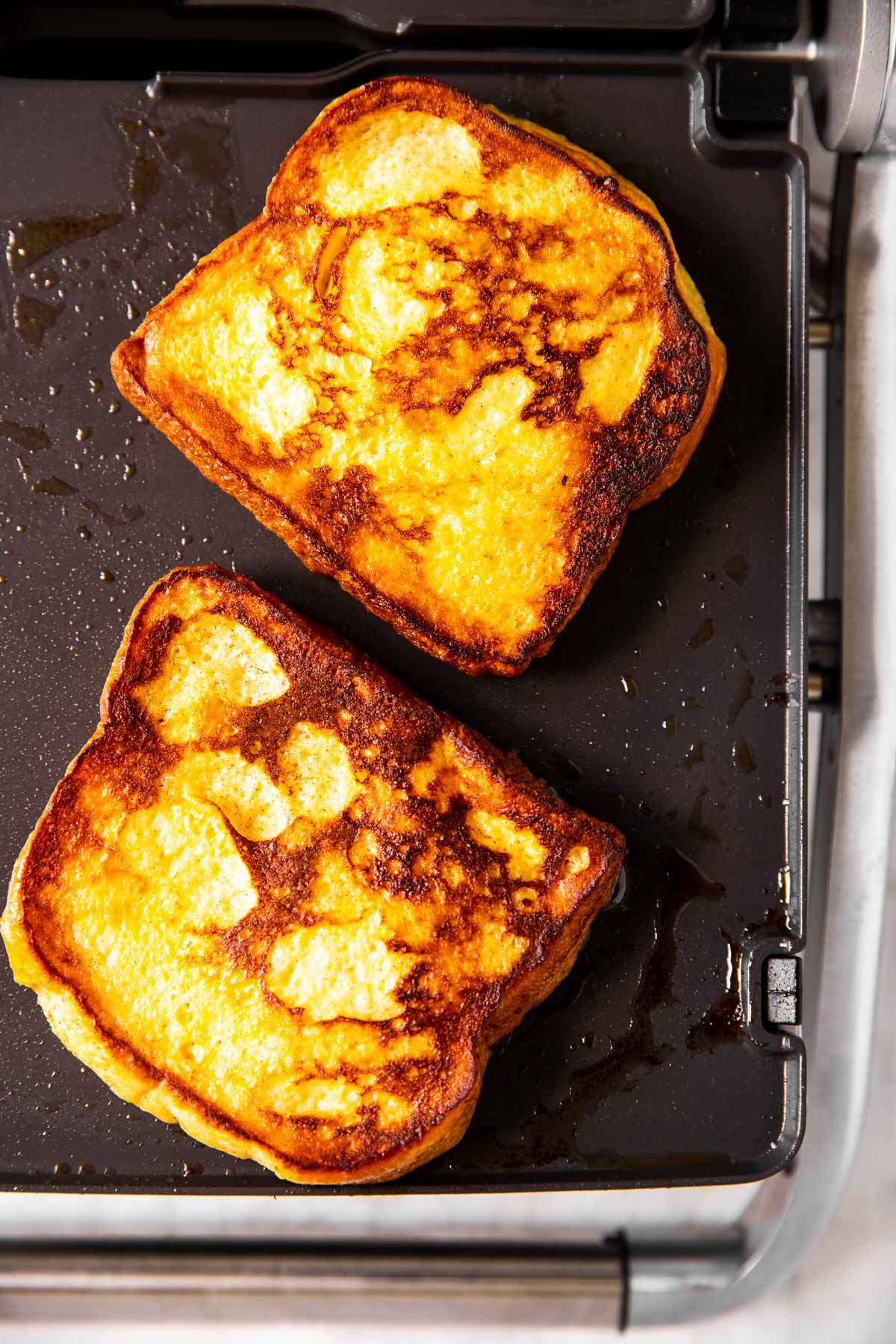 two pieces of cooked French toast on griddle