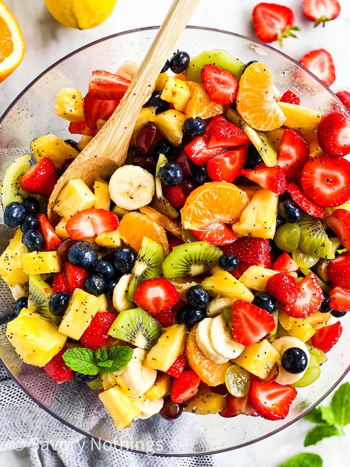 keressen egy gyümölcssalátát egy üvegtálban fakanállal, körülvéve több friss gyümölccsel