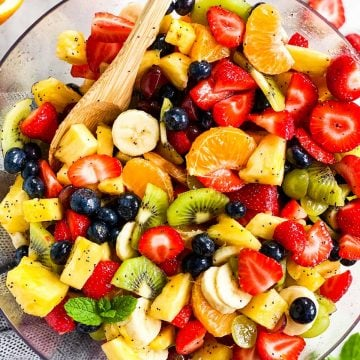 overhead view of fresh fruit salad in glass bowl with wooden spoon