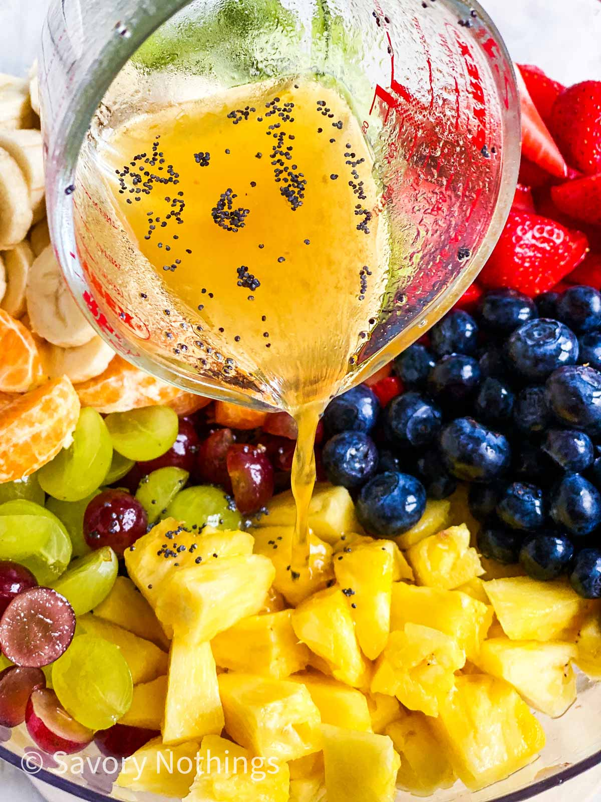 poppy seed fruit salad dressing pouring over fresh fruit in glass bowl
