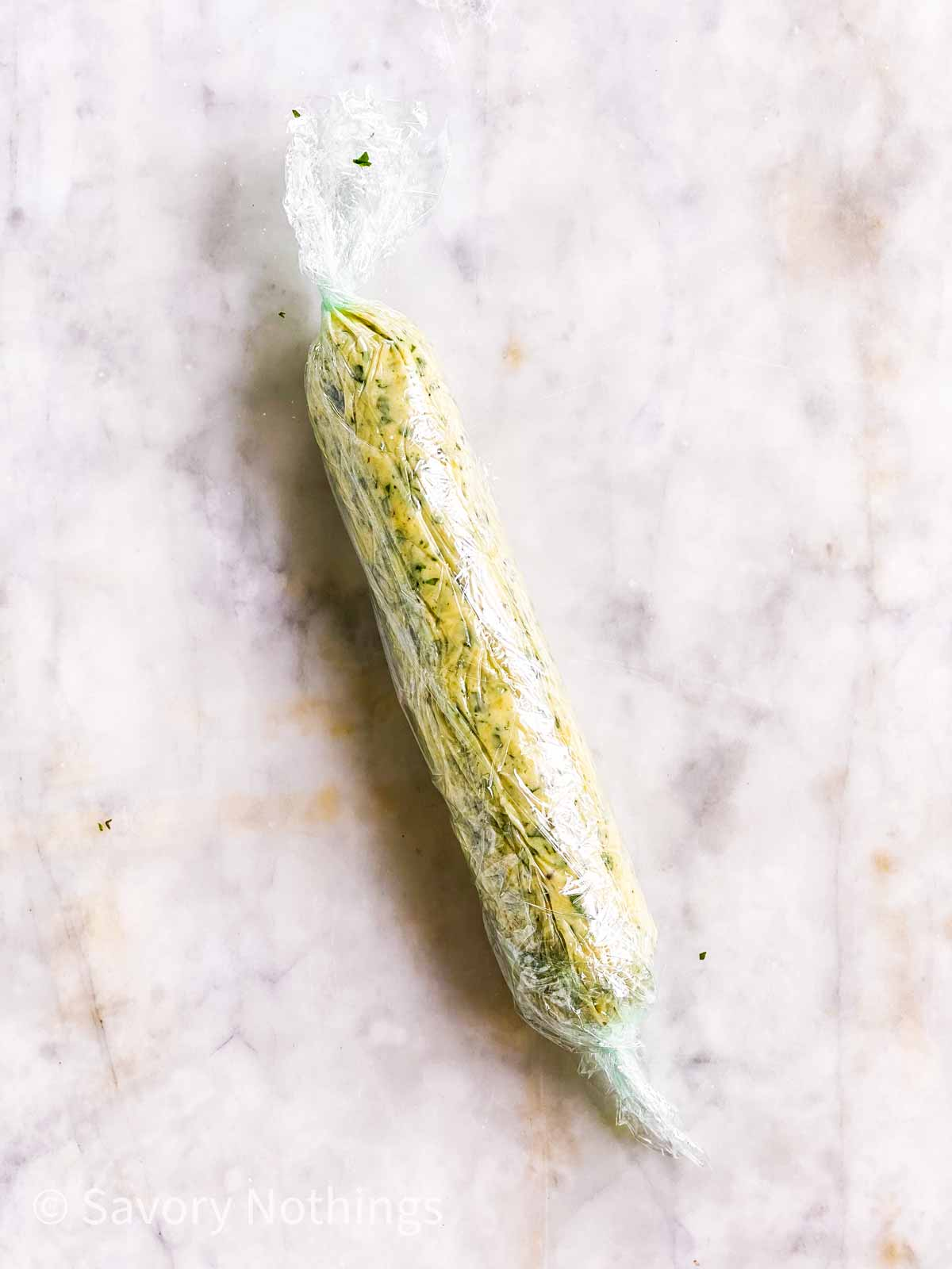 garlic herb butter wrapped in sausage shape in plastic wrap on marble surface