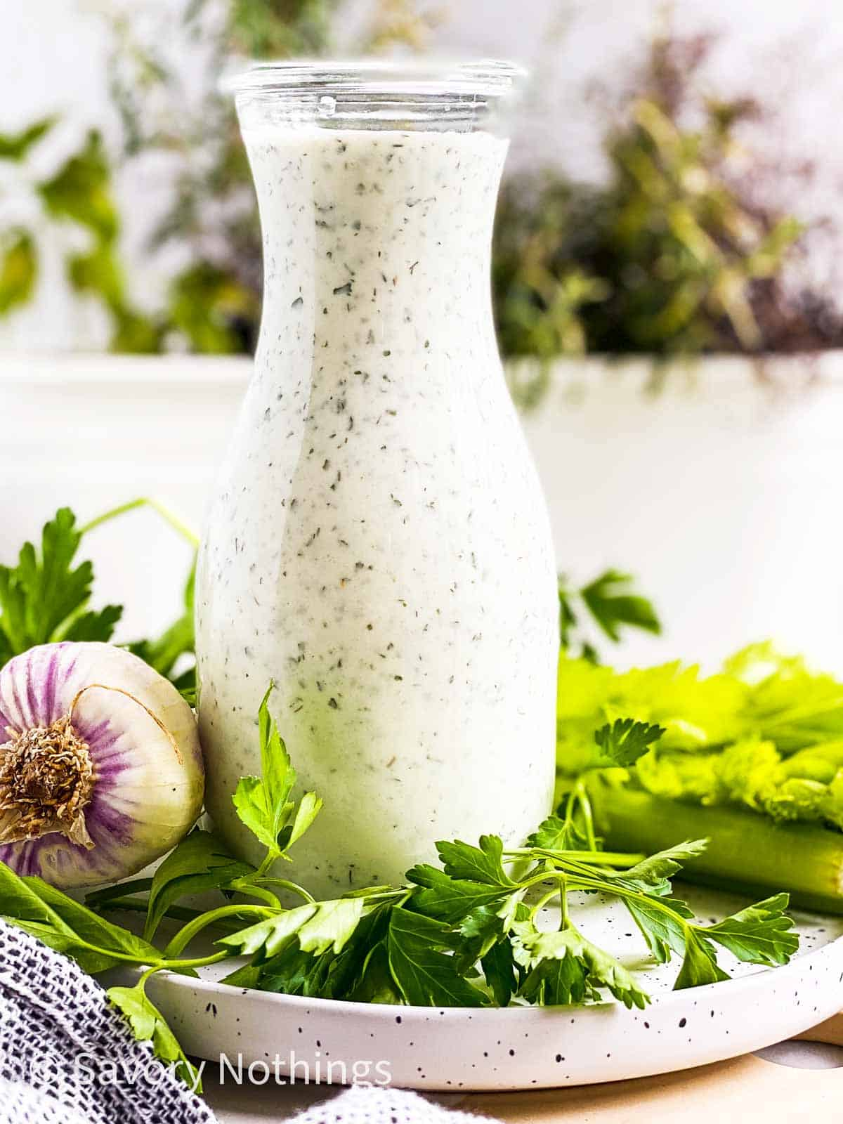homemade ranch salad dressing in glass bottle on plate with fresh herbs and garlic