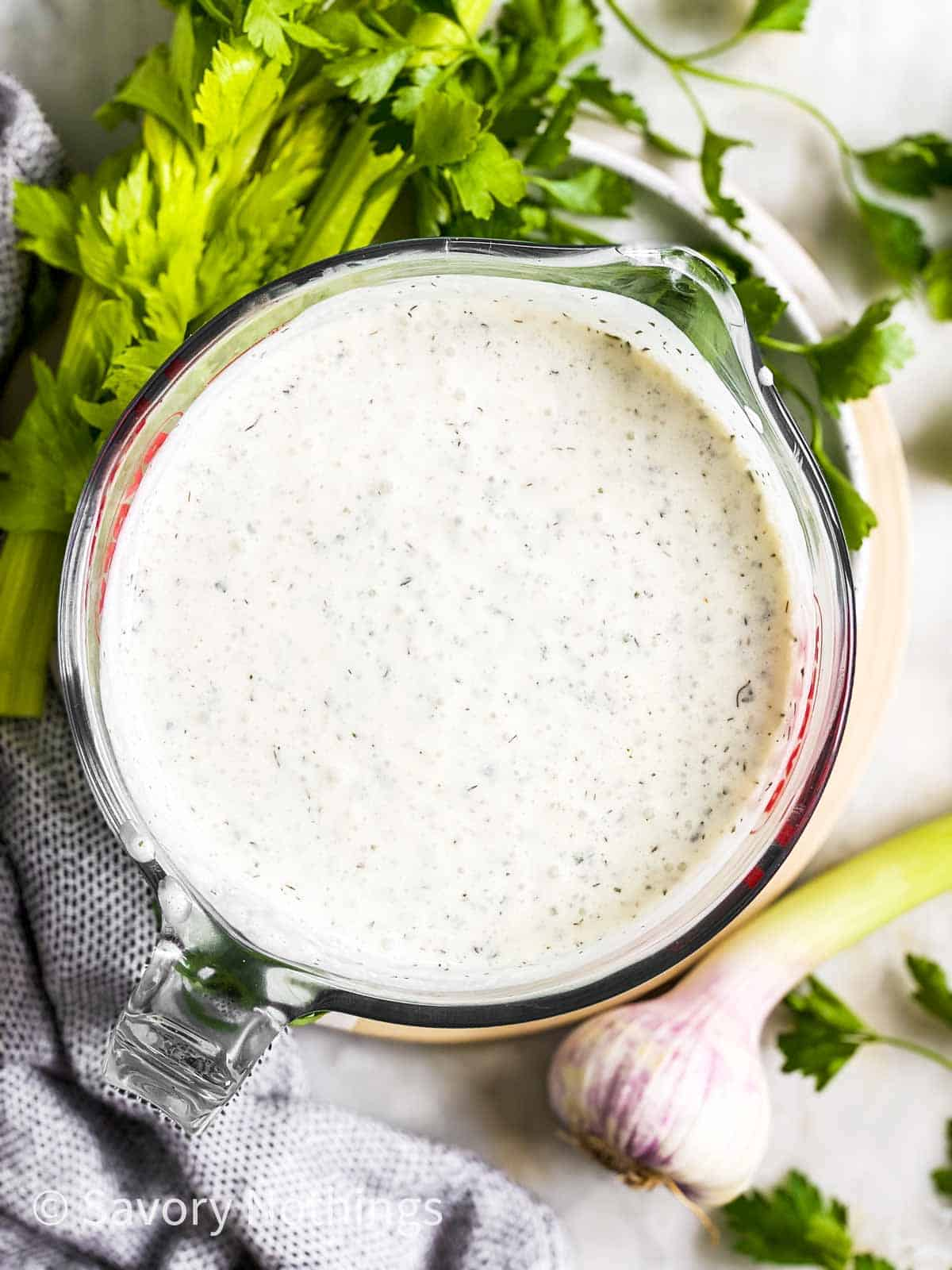 overhead view of ranch salad dressing in glass measuring jug on platter with fresh herbs and garlic