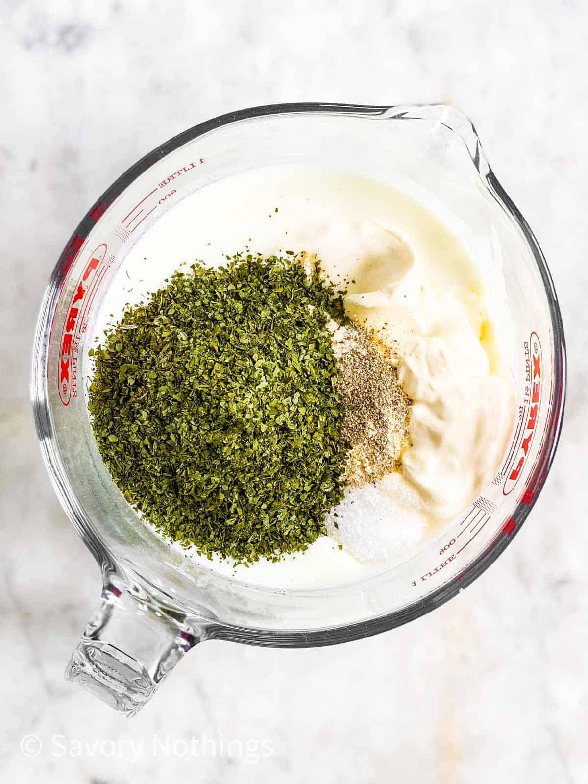 ingredients for ranch salad dressing in glass measuring jug