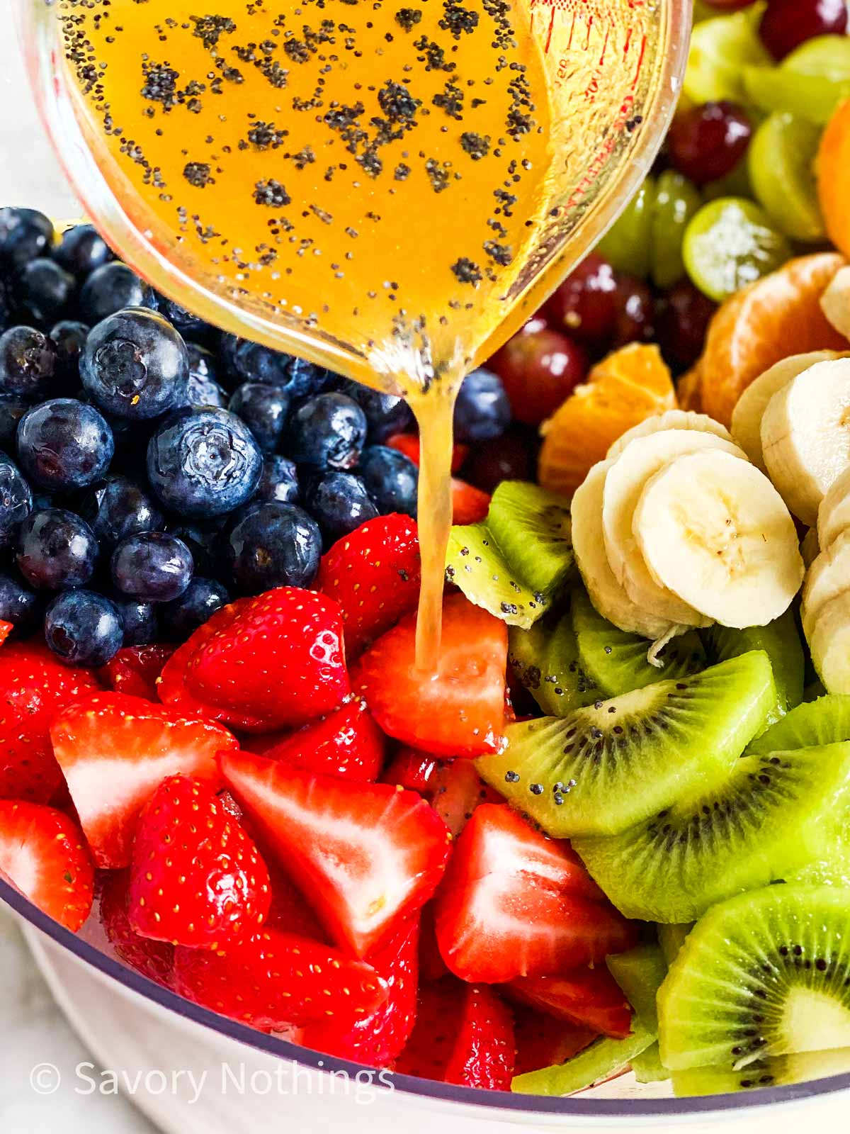 poppy seed fruit salad dressing pouring over freshly cut fruit from small glass measuring jug