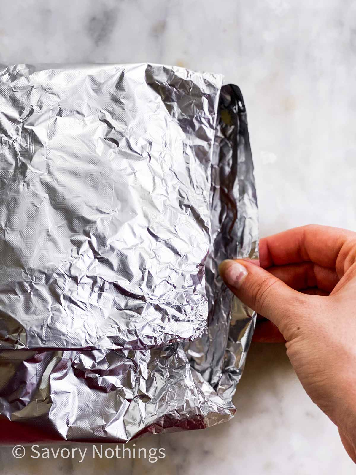 female hand pulling out edge of foil packet