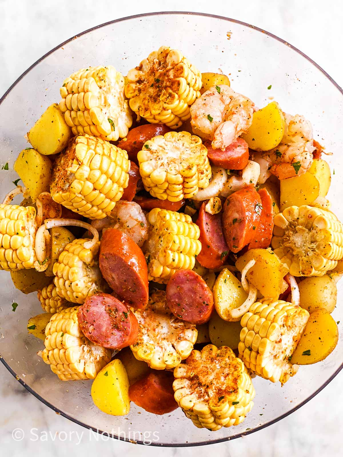 ingredients for shrimp boil foil packets combined in large glass bowl