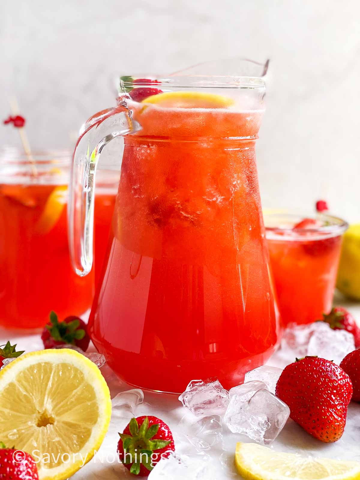 glass jug filled with strawberry lemonade surrounded by ice, strawberries, lemon and glasses full of strawberry lemonade