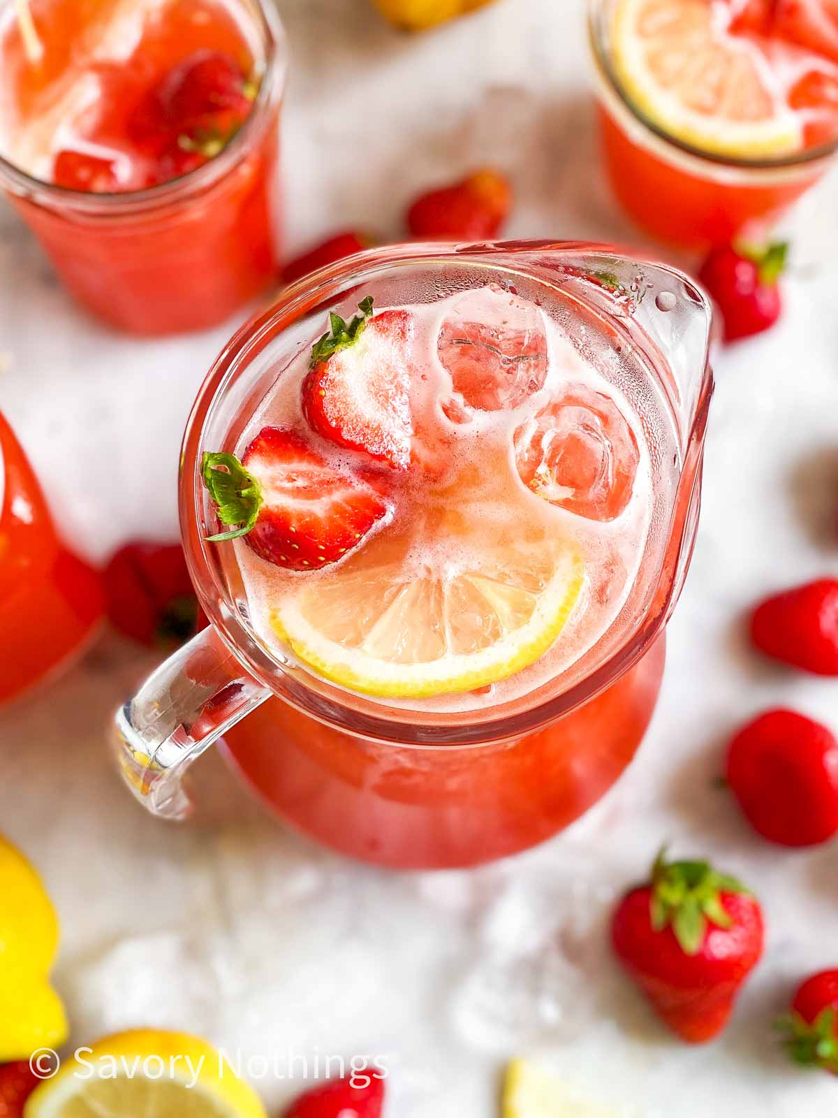angled overhead view of glass jug filled with strawberry lemonade, lemon slices, ice cubes and sliced strawberries
