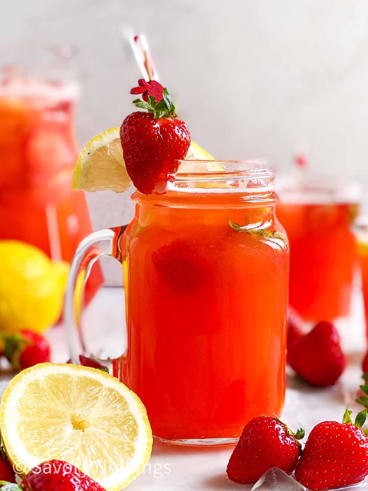 mason jar filled with strawberry lemonade and garnished with straws, fresh strawberries, ice and lemon