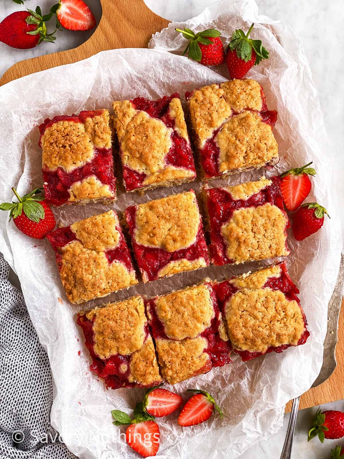 sliced strawberry oatmeal bars on white baking parchment surrounded by fresh strawberries